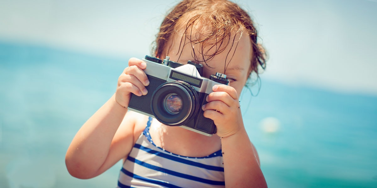A photo of a little kid at the beach taking a photo.