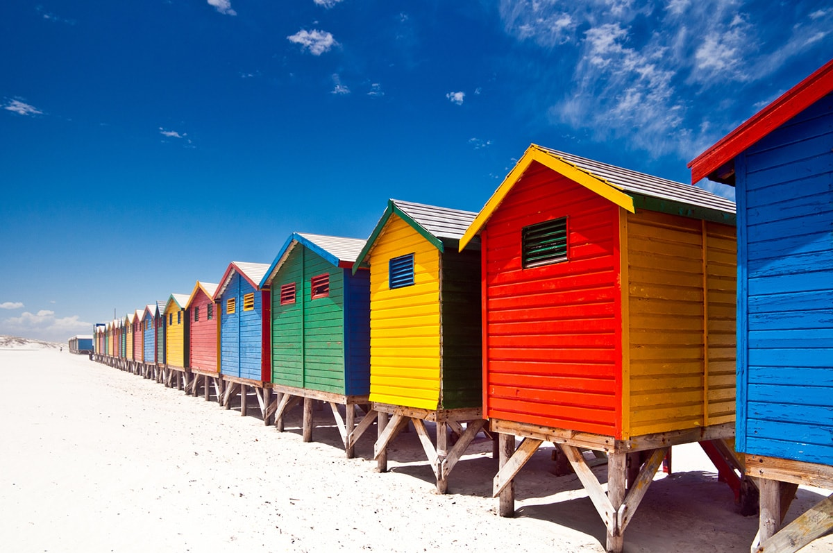 A photo of a row of brightly coloured beach huts, taken on a sunny day.