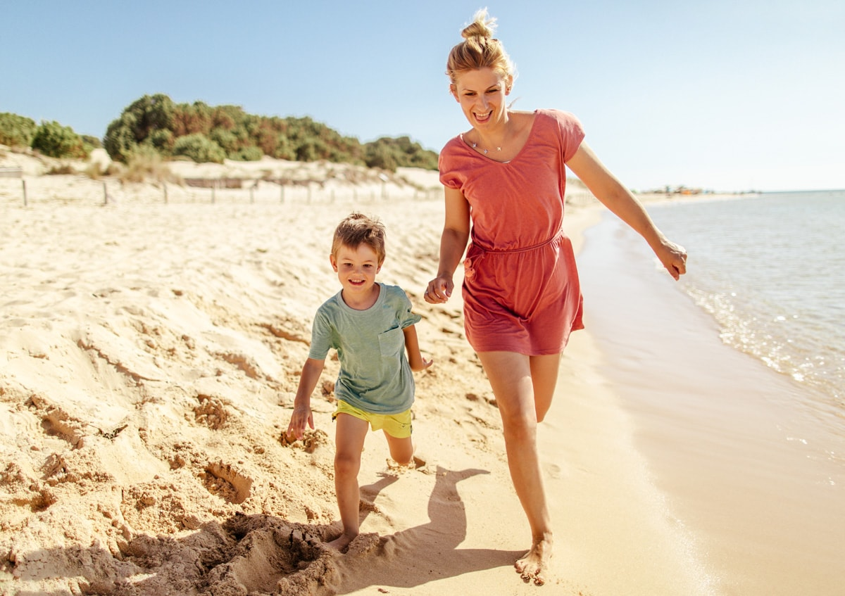 A photo of a woman and her son running along the beach.