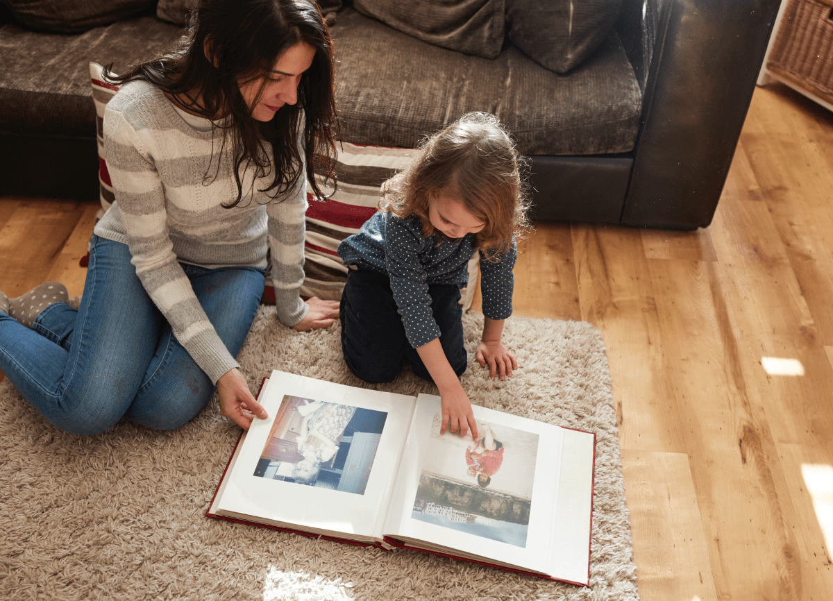 A woman and daughter looking through an old photo album on the living room floor.