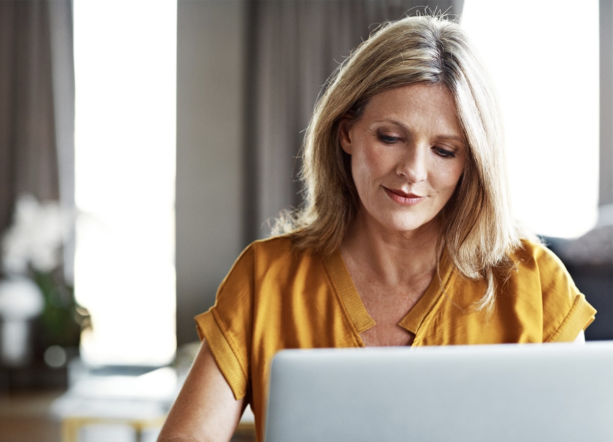 A woman in a yellow shirt sat behind her laptop in her living room.