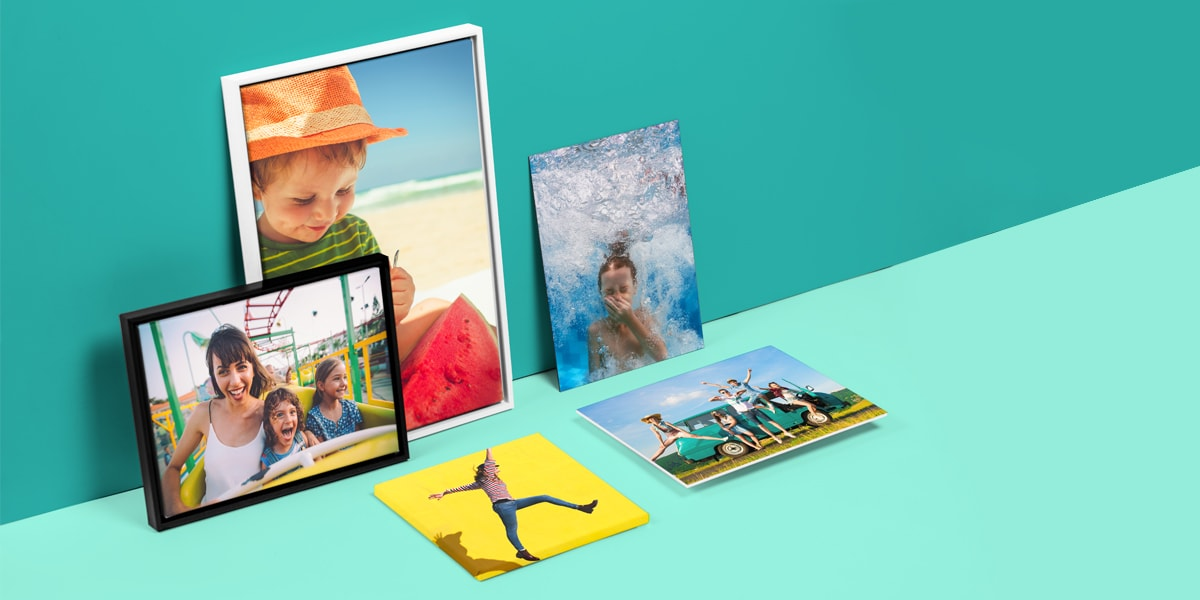 Five pieces of wall art, all featuring summery photographs, propped up against a bright teal wall.