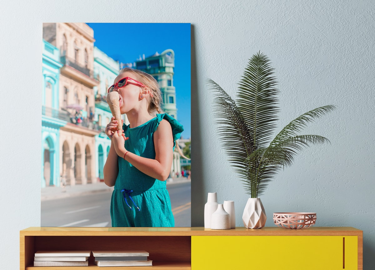 A large piece of wall art, featuring a picture of a girl eating an ice cream, on a side table, next to a plant.
