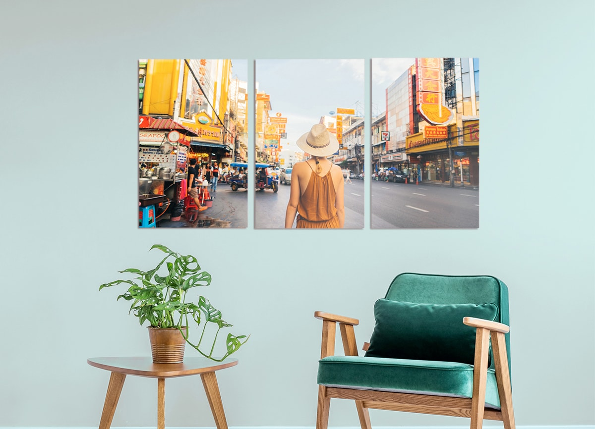 Three pieces of wall art on a light teal wall, all displaying slices of one large image of a woman on her travels in a busy city.