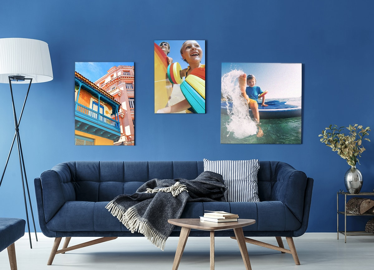 : A photo of a living room with a dark blue sofa against a dark blue wall. On the wall, there are three pieces of wall art displaying brightly coloured photos taken on a summer holiday.