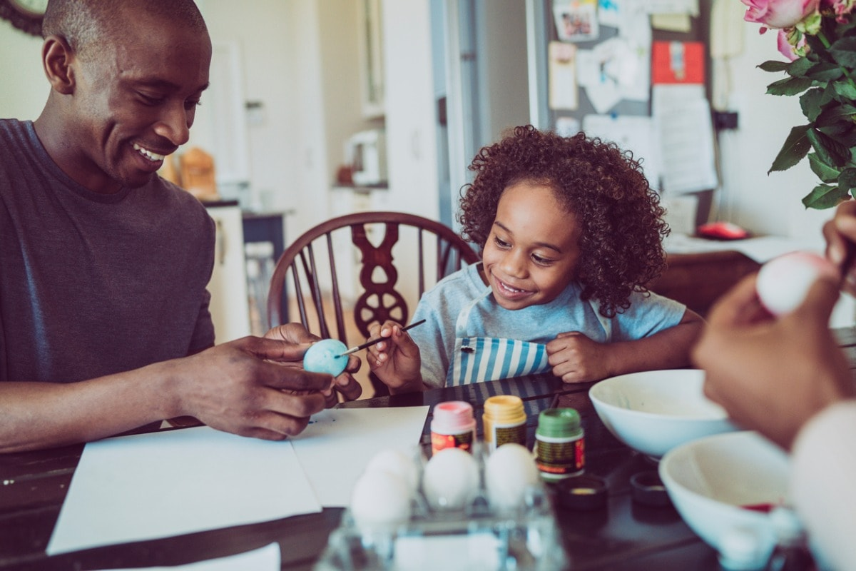 A photo of a man and his daughter painting colourful eggs around a kitchen table.