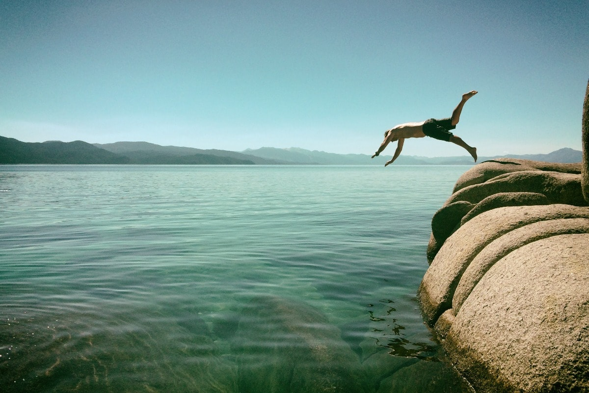 A photo of a man diving off a rock into the see on a sunny day.