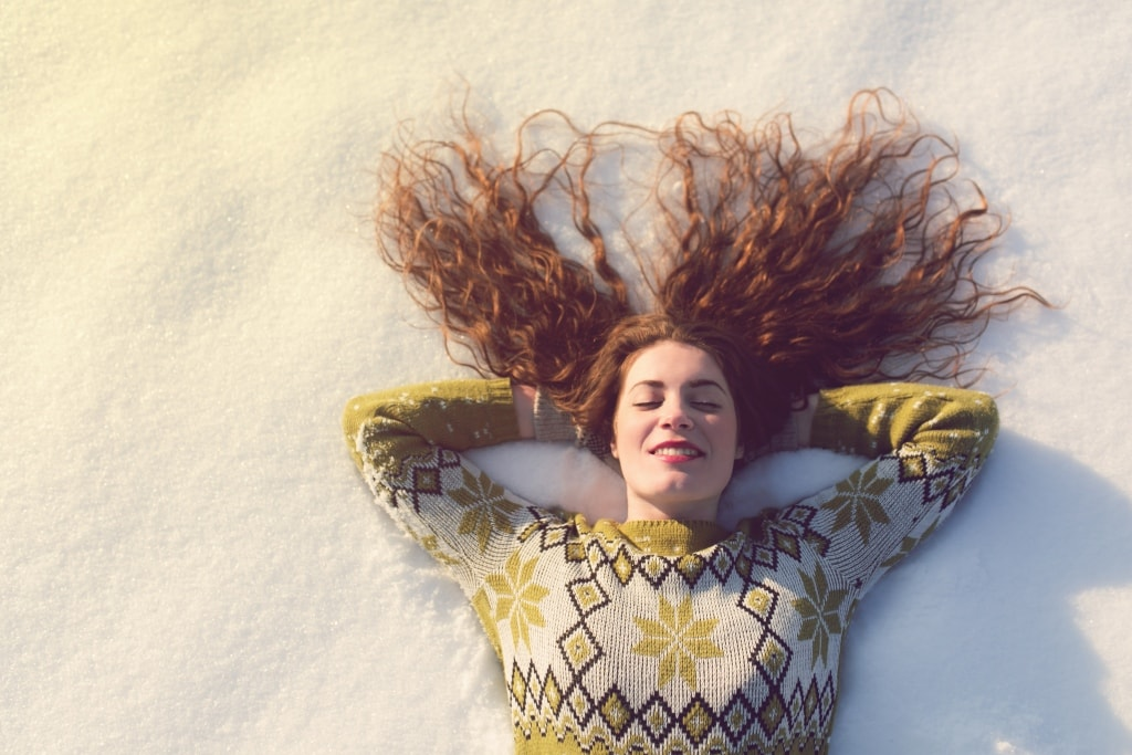 A woman in a festive jumper lying in the snow on a sunny day.