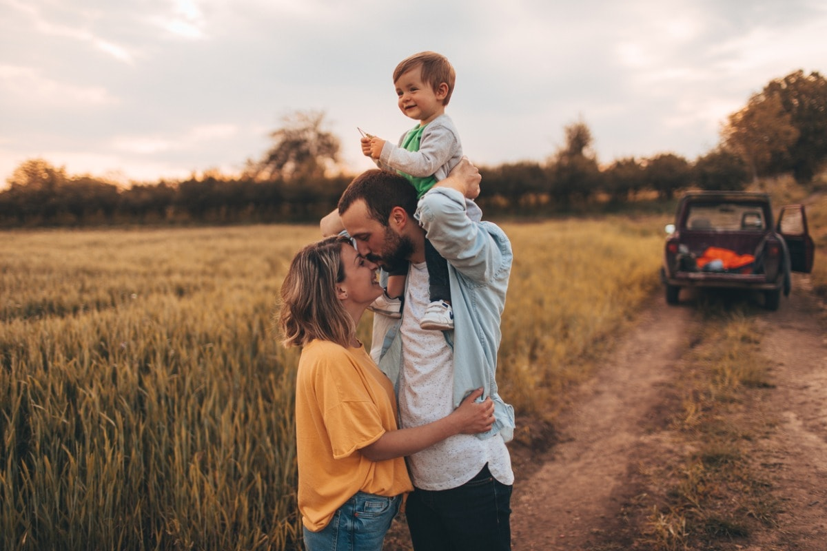 A photo of a man and a woman out in the countryside with their son sitting on the man's shoulders.