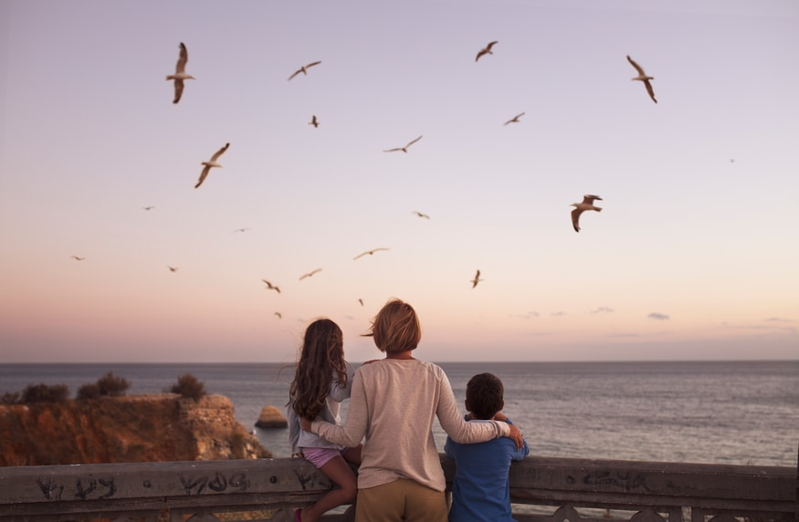 A woman at the coast with two kids, looking over the water at sunset with birds in the sky.