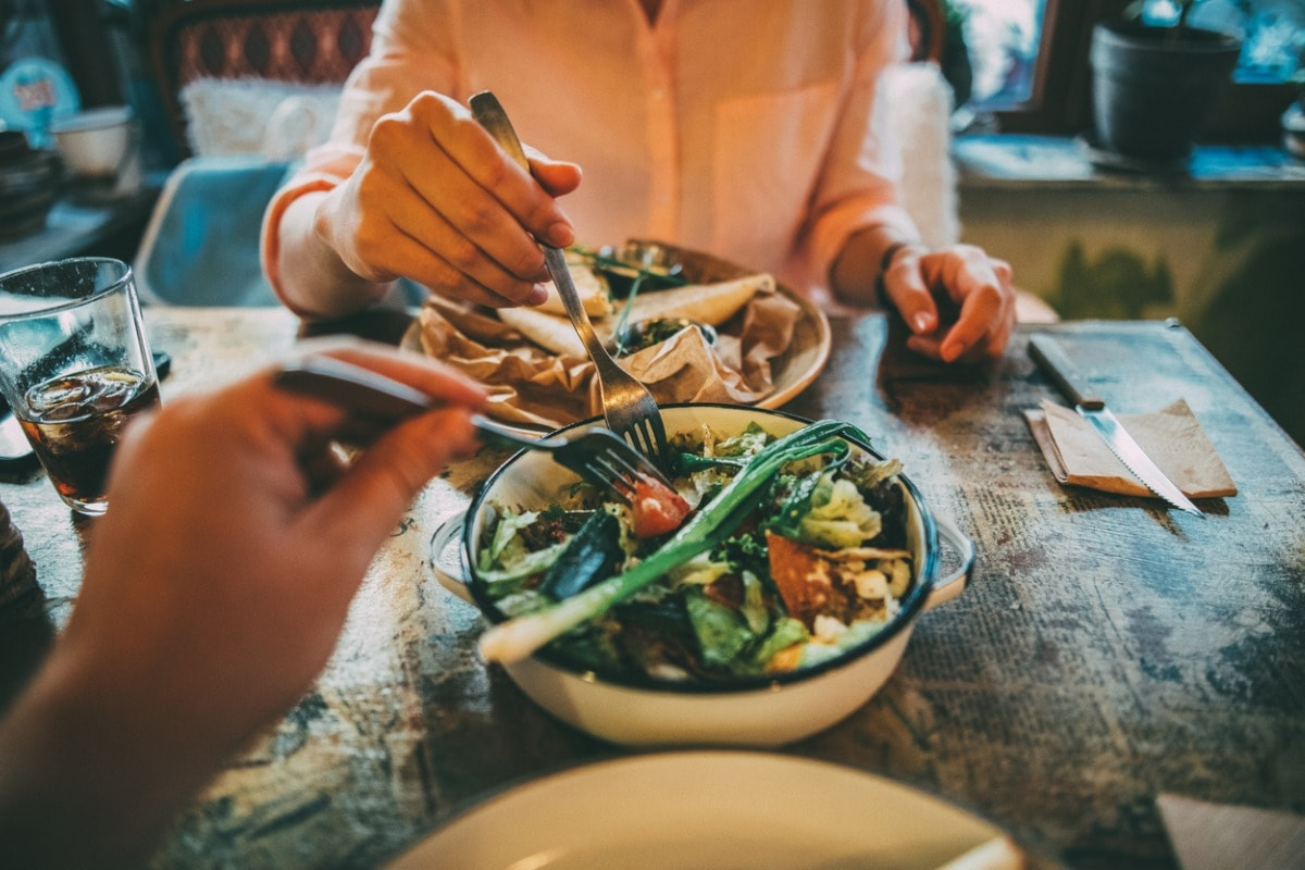 Two people sat at a table in a restaurant, sharing a large bowl of food.