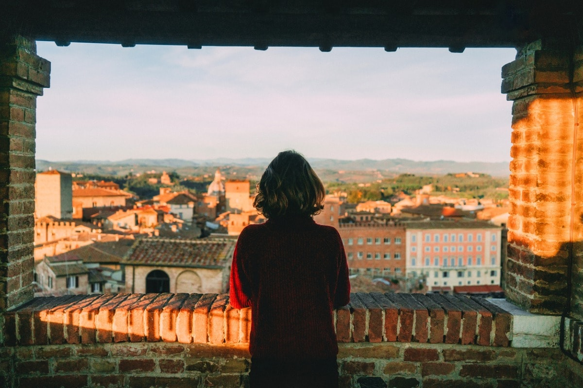 A woman with her back to the camera, looking out of an old tower across a historical town.