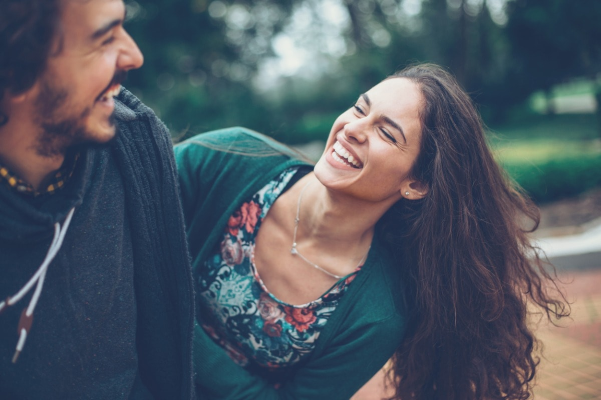 A photo of a man and a woman out in a park laughing together.