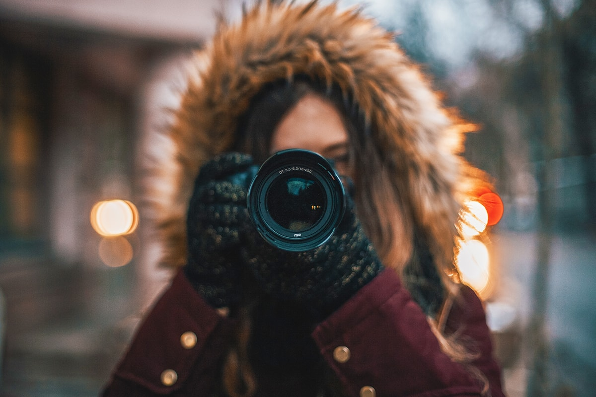 An image of a woman wearing a parka taking a photo with a DSLR camera.