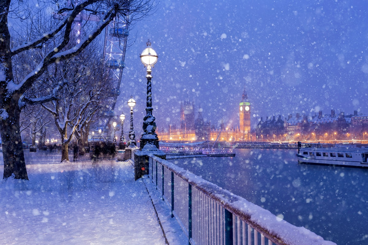A photo of snowfall over London at night, with Big Ben in the background, slightly out of focus, and the London Eye in the left-hand corner.
