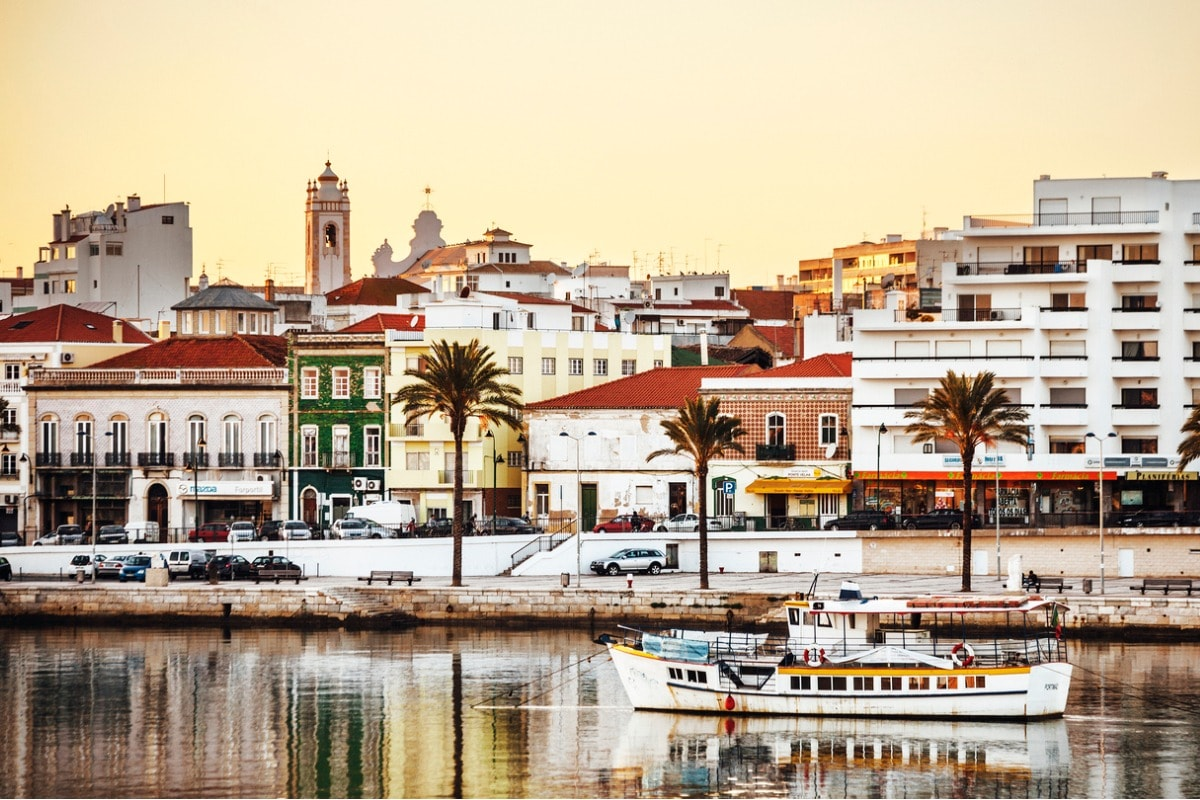 A photo of a port in the Algarve, taken at sunset, with a small boat in the foreground.