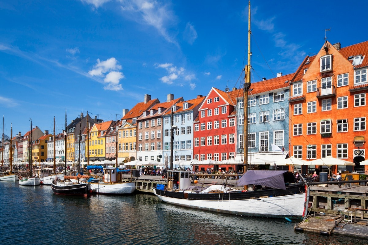 A photo of Copenhagen's brightly coloured buildings at the port, with small sailing boats moored up on the dock.
