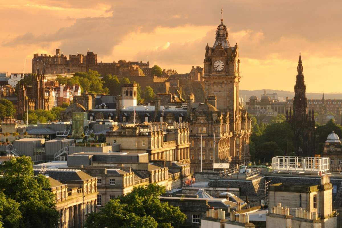 A photo of Edinburgh taken at dusk. The castle is in the background on the left of the image.