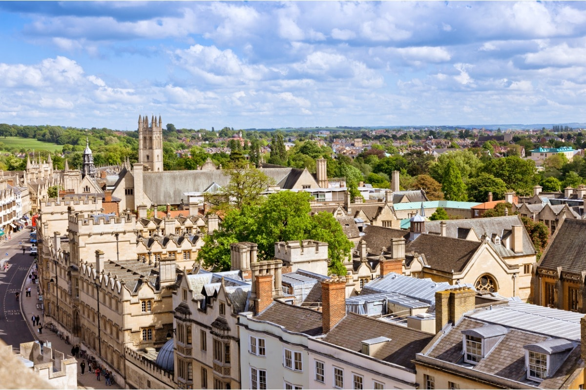 A photo of Oxford's rooftops and the belltower of the city's cathedral, with trees and hills in the distance.