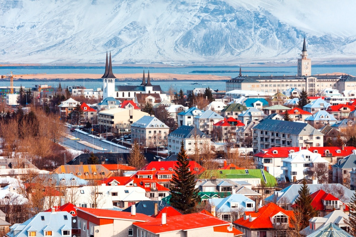 A photo of brightly coloured rooftops in Reykjavik, taken with the water's edge in the background and a snowy mountain in the distance.