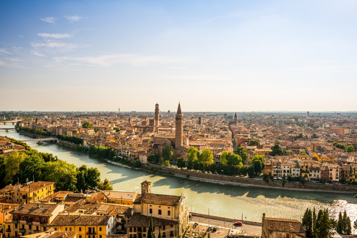 A photo of Verona's rooftops and the river running through the city, taken on a bright and sunny day.
