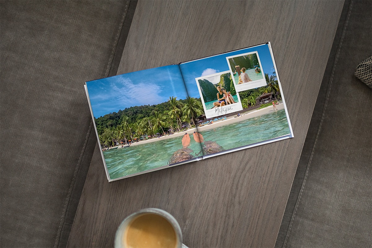 A photo book open on a wooden tabletop. There's a double-page spread image