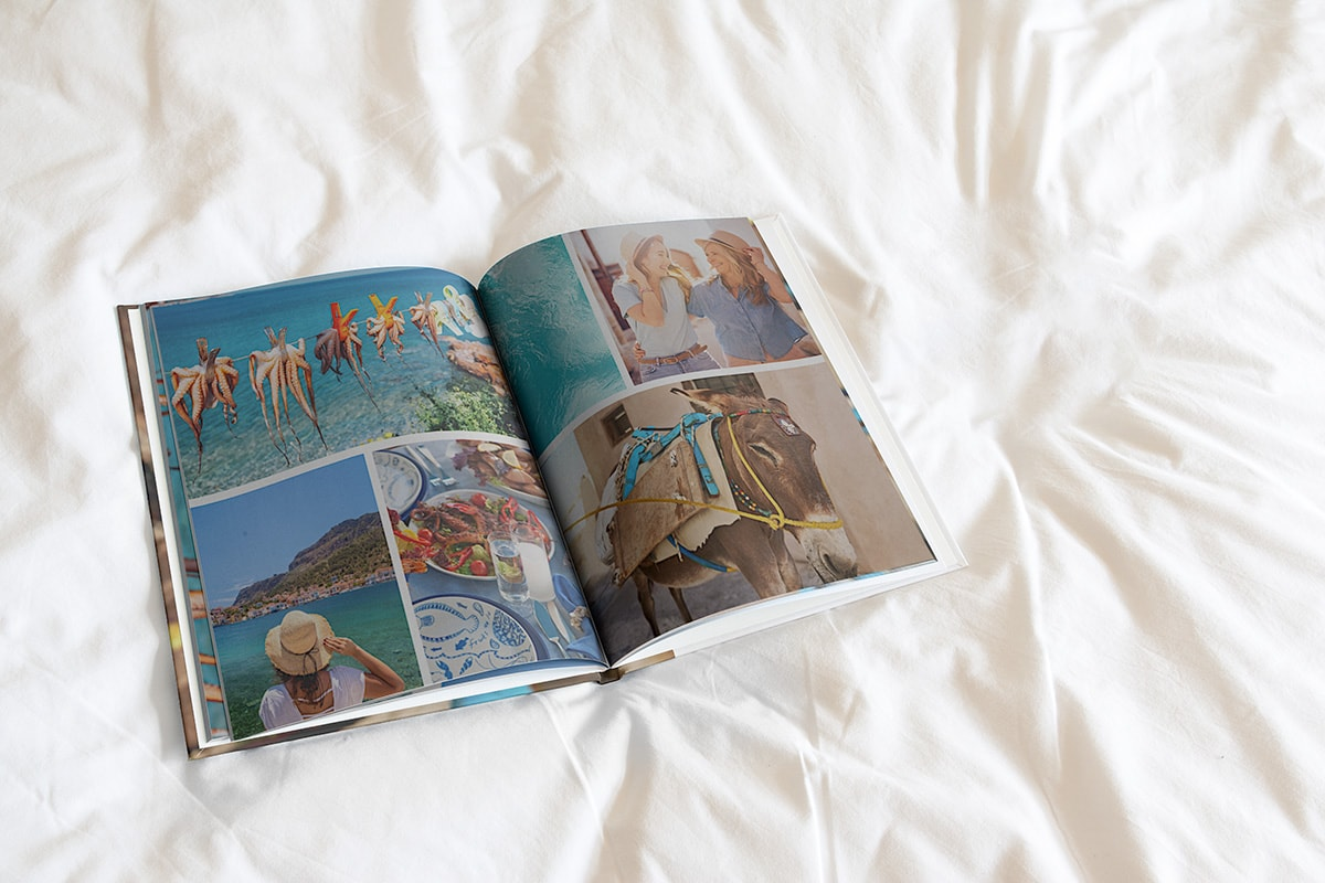 : A woman's hands flipping through a layflat photo book that has one large photo of a pool at sunset overlapping across two pages, with a smaller instant camera-style photo on a teal background on the edge of the left-hand page.