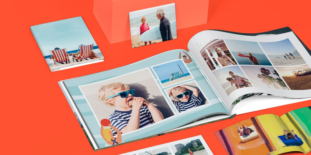 A selection of five photo books on a bright orange surface, all open, showing summery photos on the pages.