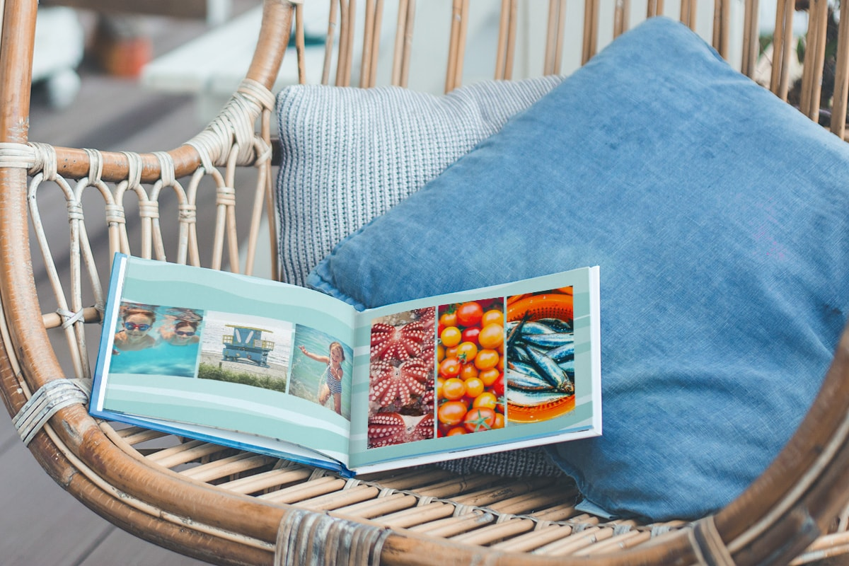 A summer photo book open on a wicker chair with blue cushions on. There are summer holiday photos on the left page and summery food photos on the right.