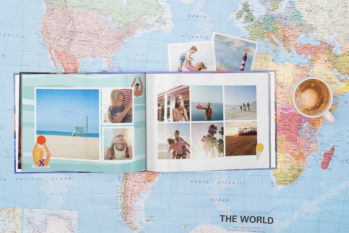 A summer pre-designed photo book open on a map. There's a cup of coffee next to the book and summer photo prints tucked behind the photo book.