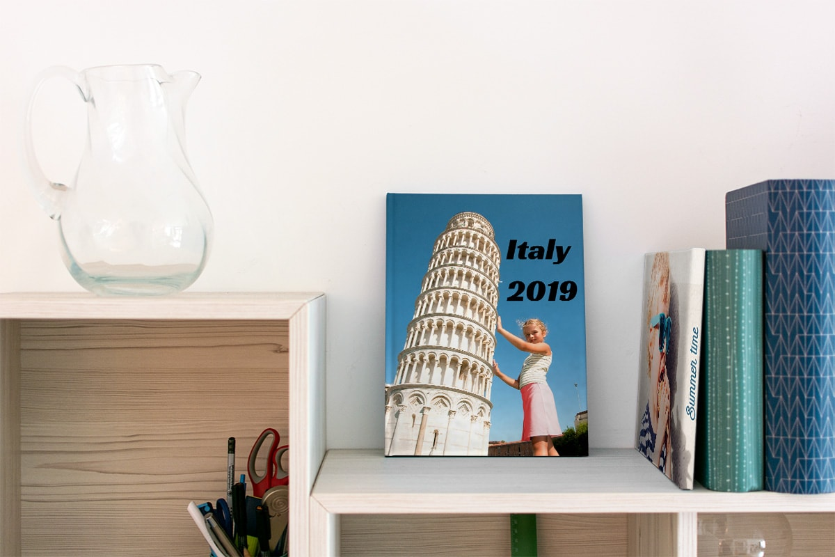 A summer photo book on a bookcase, with a little girl on the cover posing as if she's pushing the Leaning Tower of Pisa.