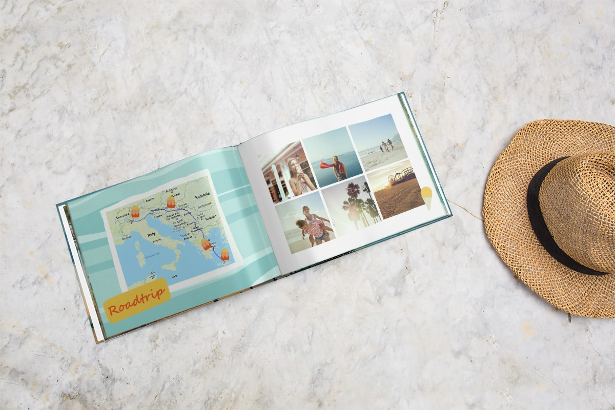 A travel photo book open on a marble tabletop. There's a map on the left-hand page, with locations plotted with ice lolly clip art. On the right page, there's a grid of six holiday photos.