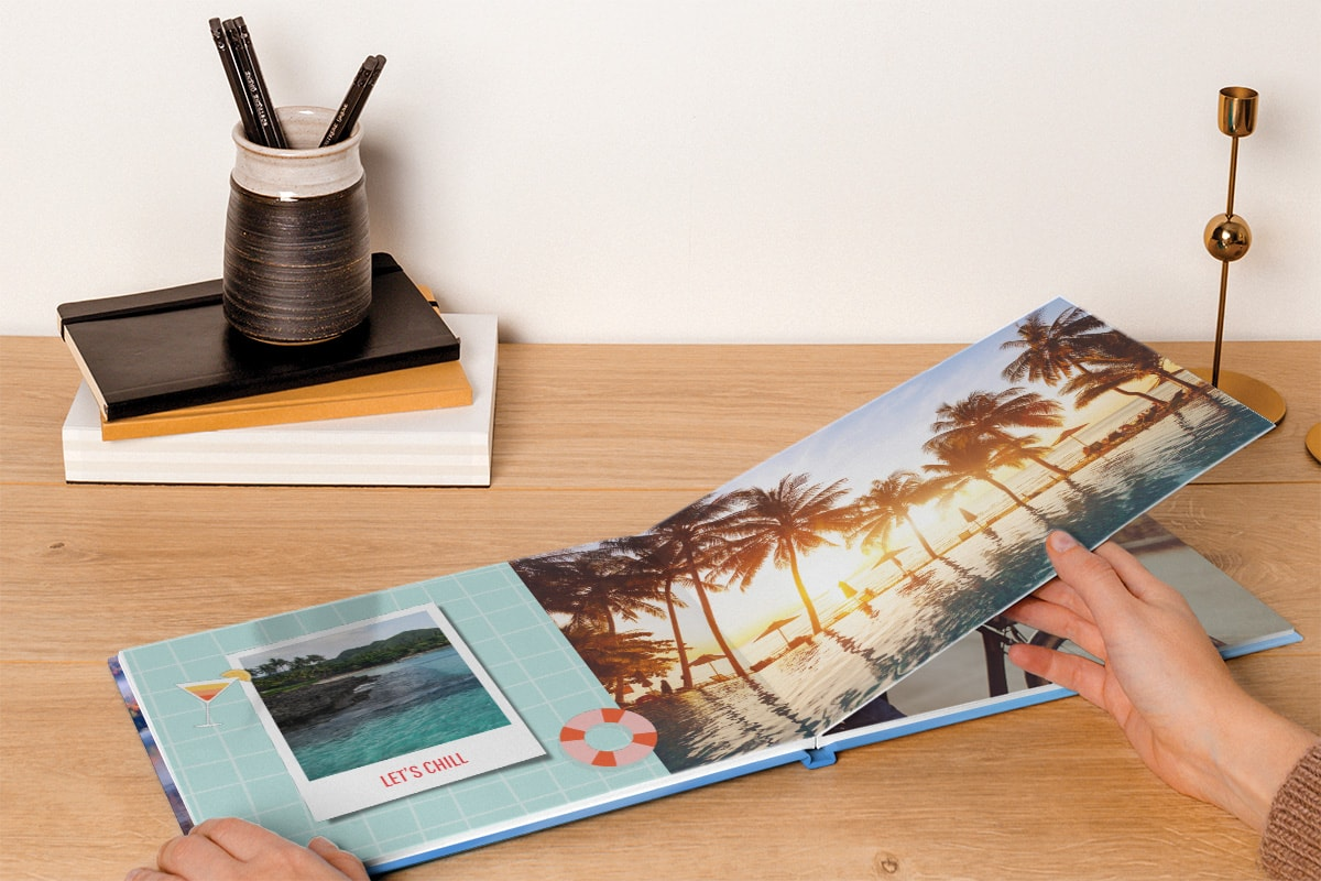 A photo book open on a wooden tabletop. There's a double-page spread image of a woman floating in the sea with a beach and palm trees in the background, and two instant camera-style images in the top right corner.