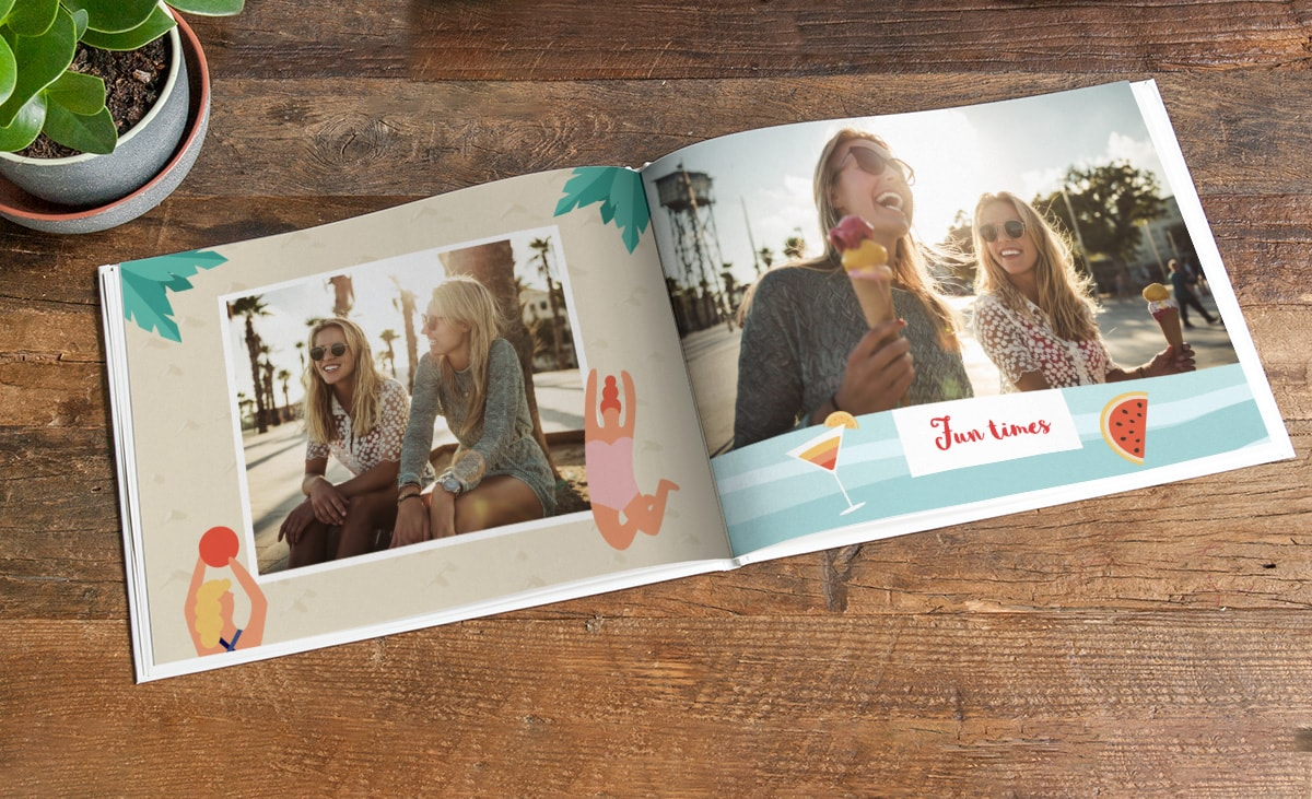 A photo book open on a wooden table. There are summery pictures of two friends on both pages that are framed by summer-themed clip art of watermelon, cocktails, palm leaves, and people in swimming costumes