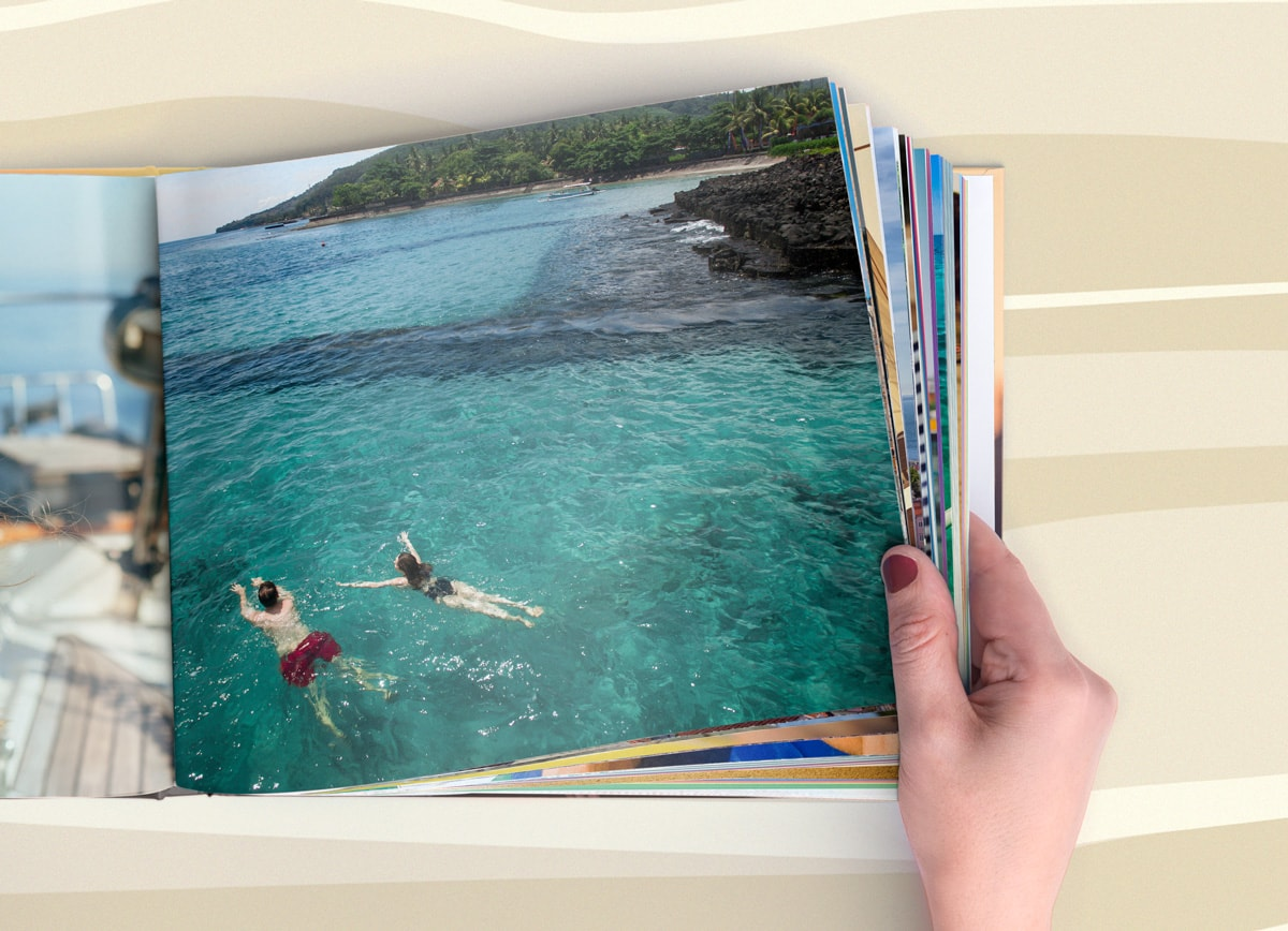A hand flipping through a summer photo book with extra pages in.