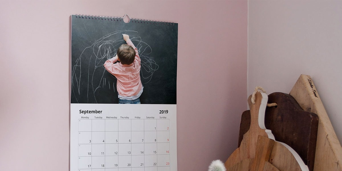 A picture of a photo calendar on a pink wall, with a photo of a little boy drawing on a chalk board on it.