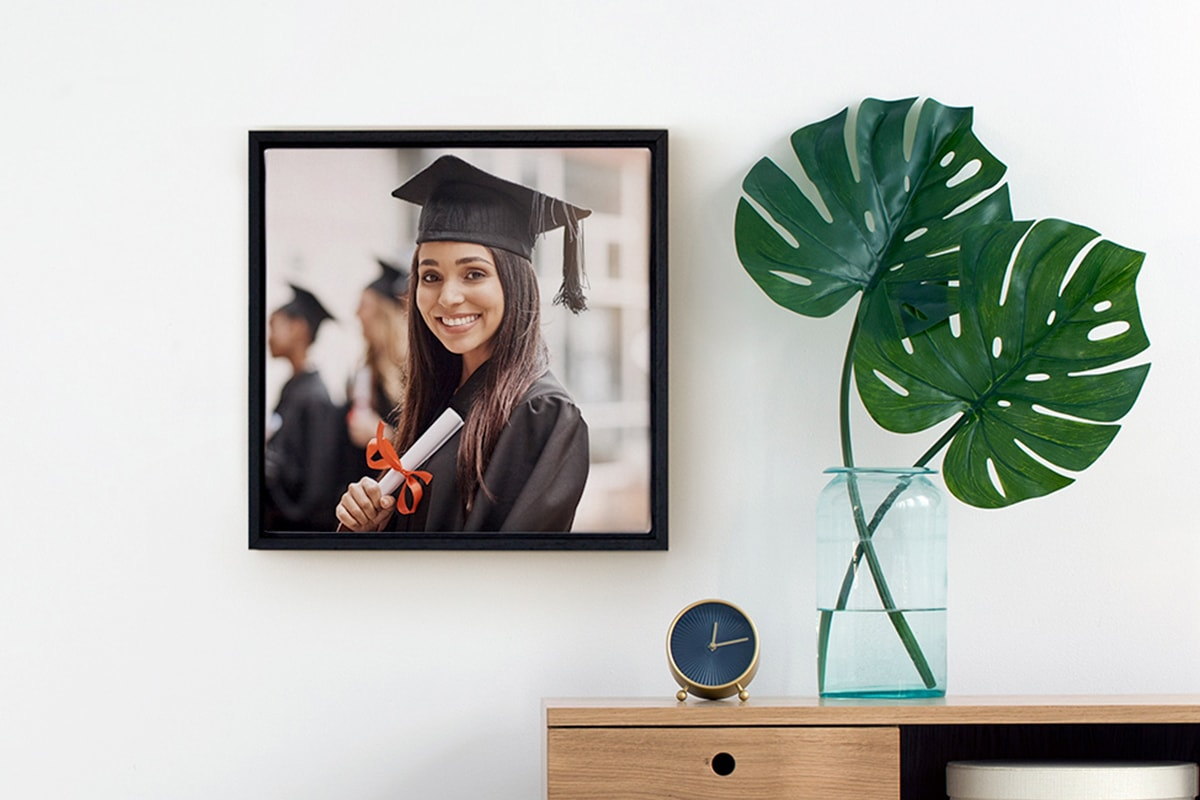 A photo of a framed canvas wall art with a girl's graduation photo on. It's hanging on a wall next to a side table with a vase on.