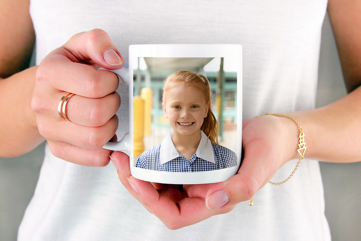 A woman holding a photo mug with a picture of a little girl in a school summer dress on the mug.