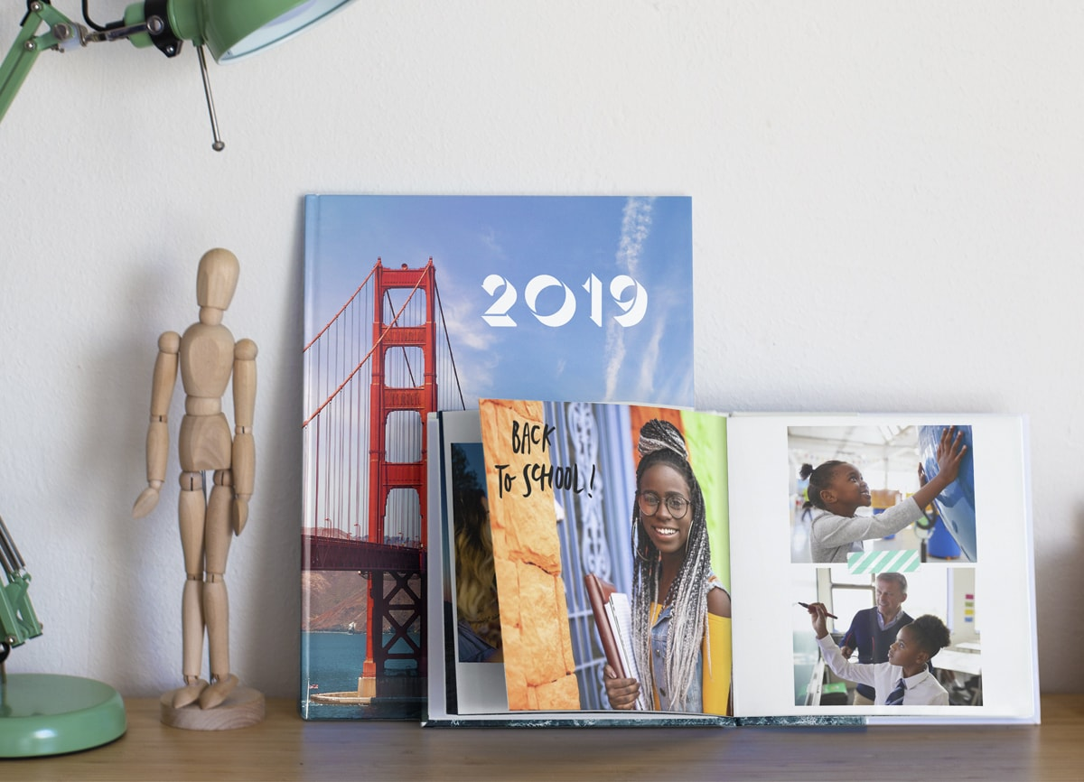 Two photo books on a shelf. The one in the background shows a photo of San Francisco on the cover, and the one in the foreground is open on a double page showing pictures of a young girl at different stages of school life; with a photo of her at college, one at nursery school, and another at school.