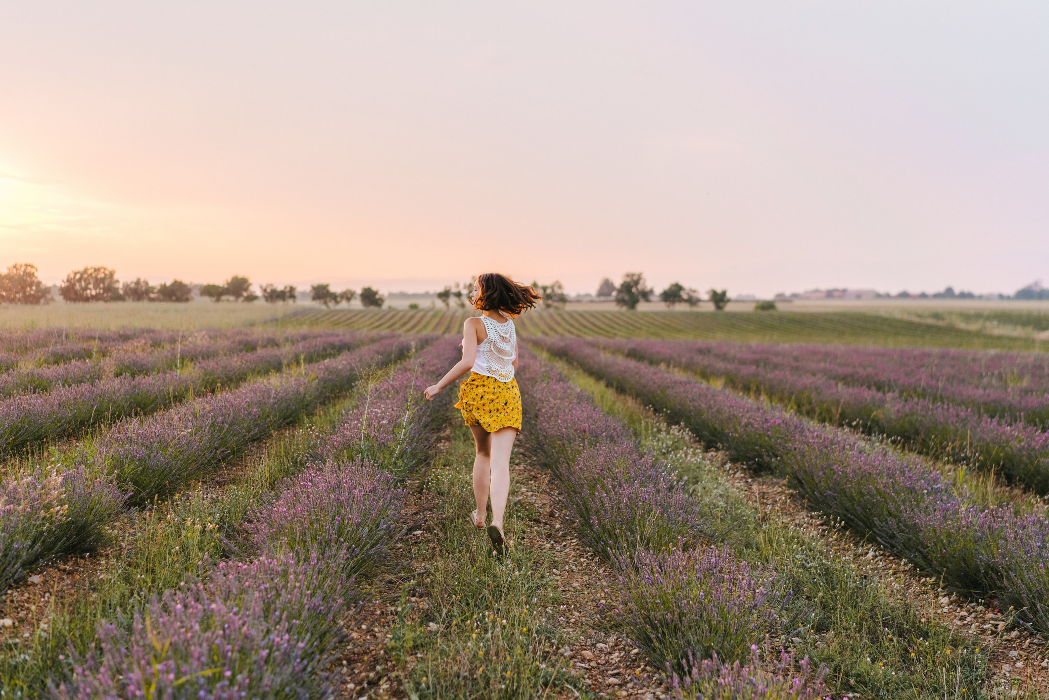 Image of a girl running through a field of purple flowers