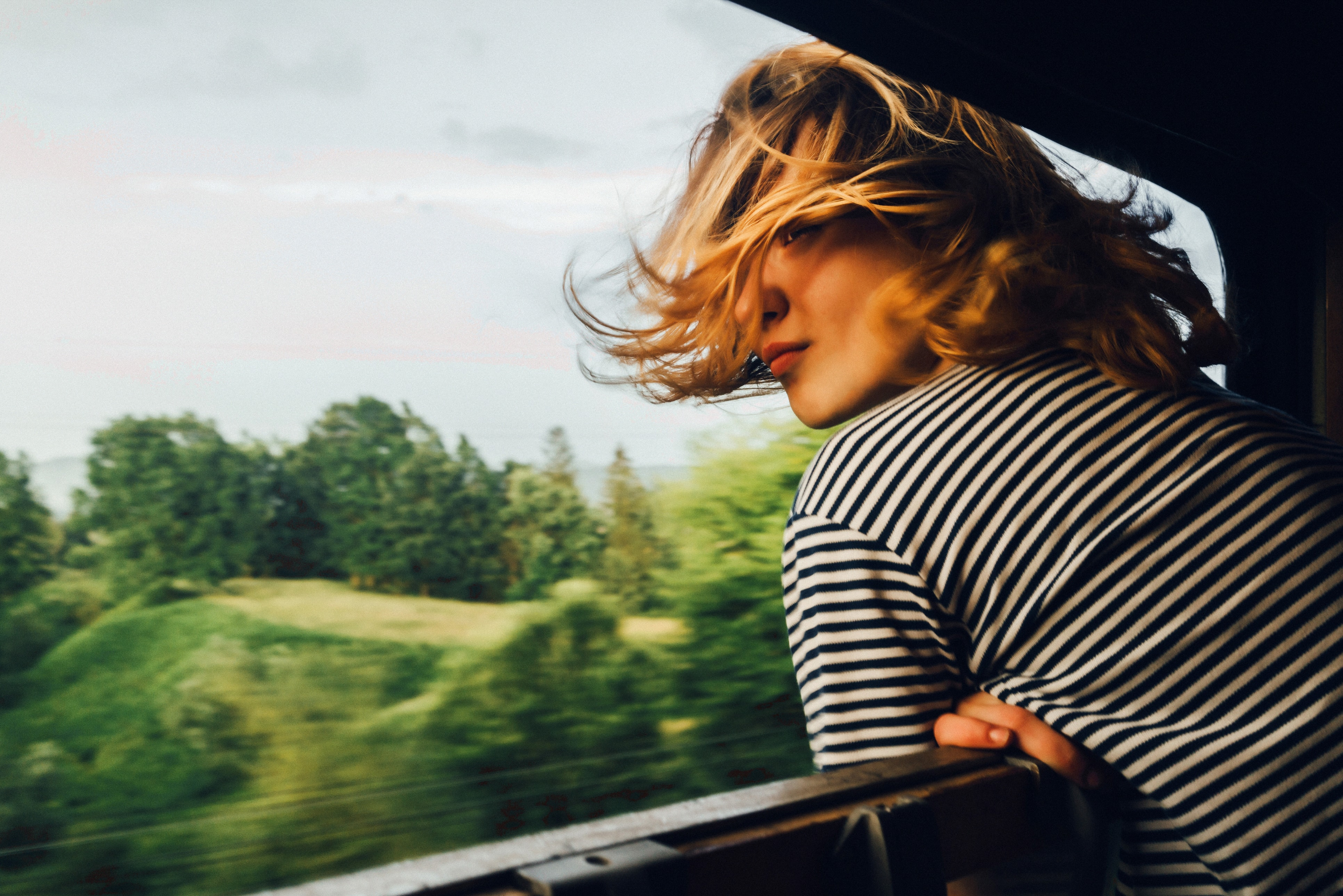Image of a girl looking out of a fast-moving train with a blurry background