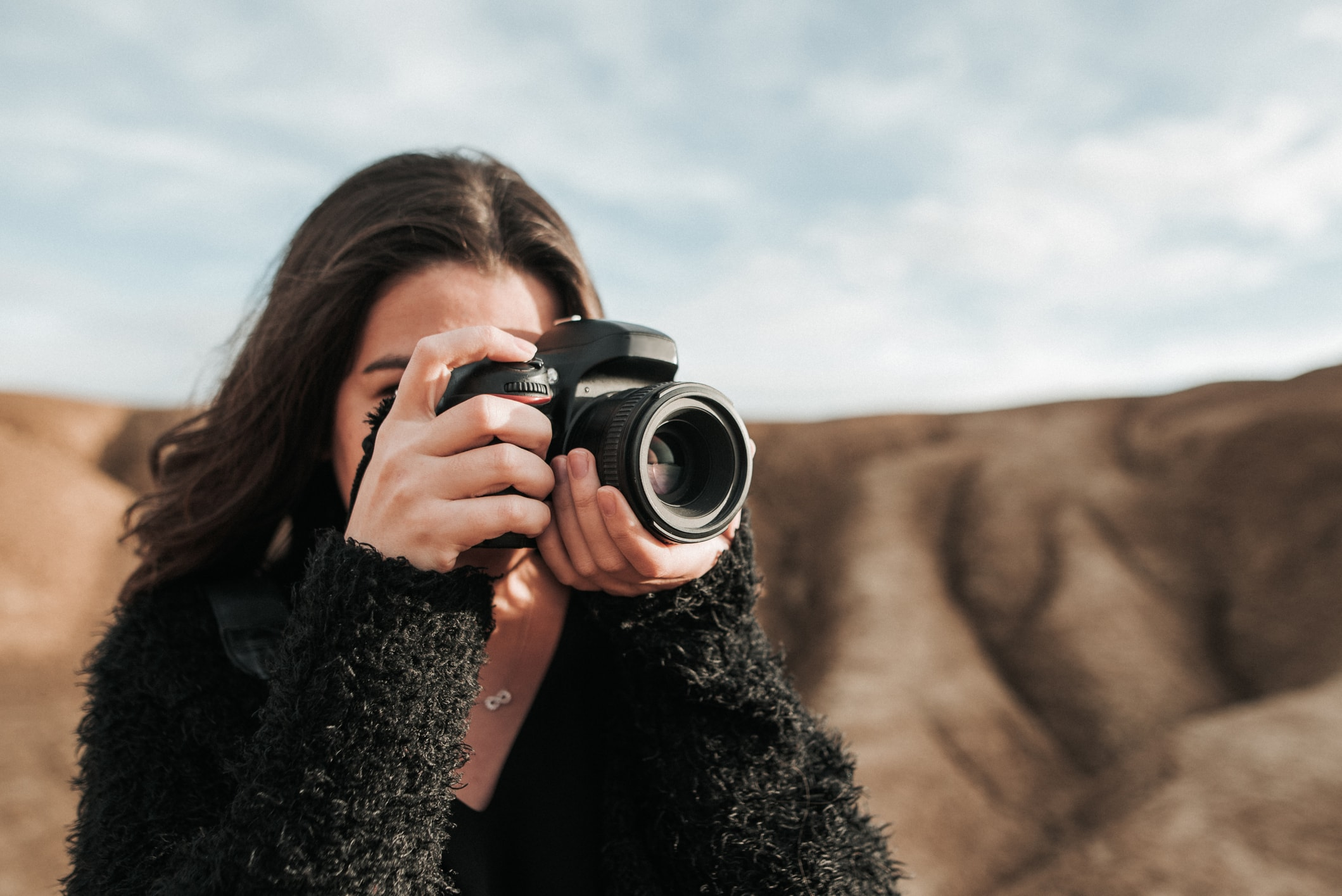 Image of a girl taking a photograph with a DSLR camera in front of a rocky background
