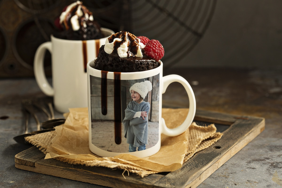 Two photo mugs with wintery photos on with chocolate mug cakes inside and whipped cream and chocolate sauce on top