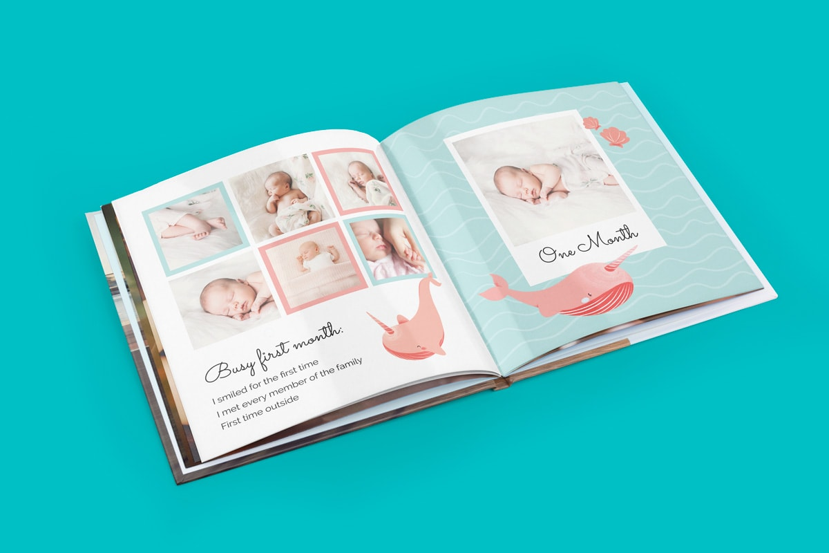 A baby photo book open on a teal background, with baby photos inside from the baby's first month. Includes a sea theme with pink shells and pink whales illustrations.