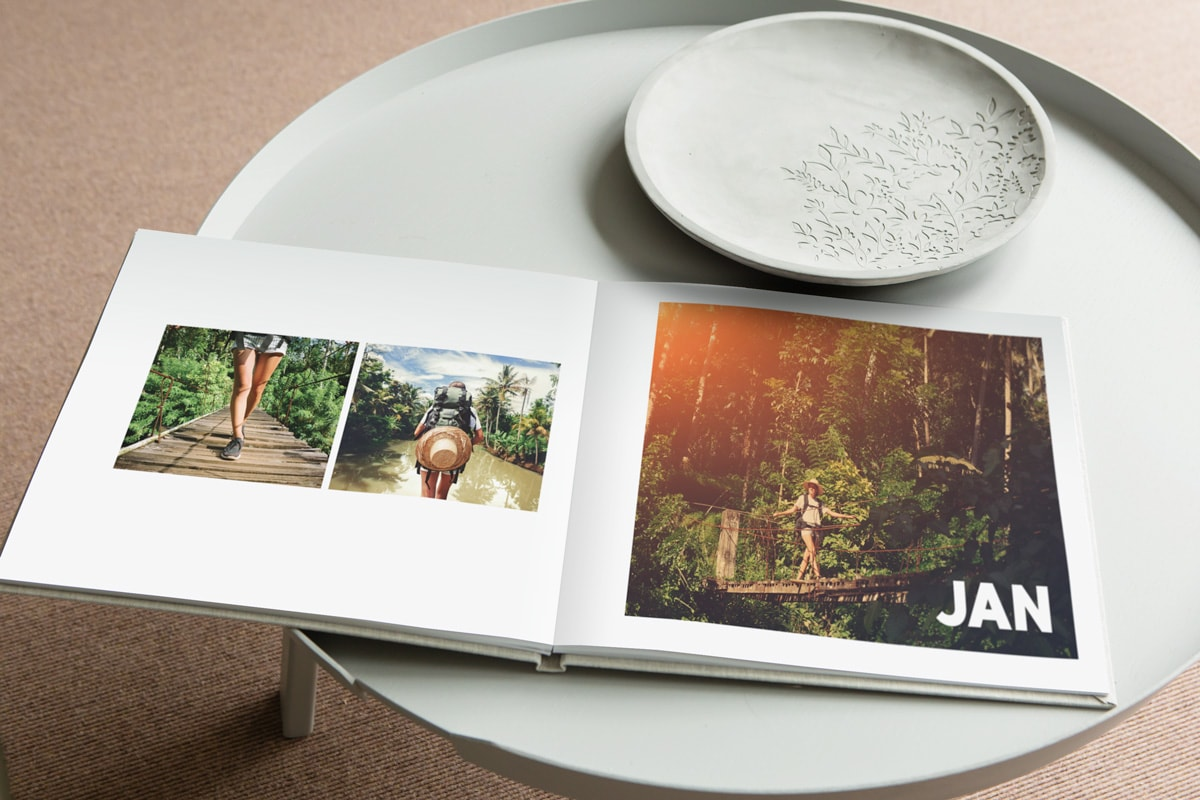 A travel photo book open on a white coffee table, showing three pictures of a young woman in a rainforest setting.A travel photo book open on a white coffee table, showing three pictures of a young woman in a rainforest setting.