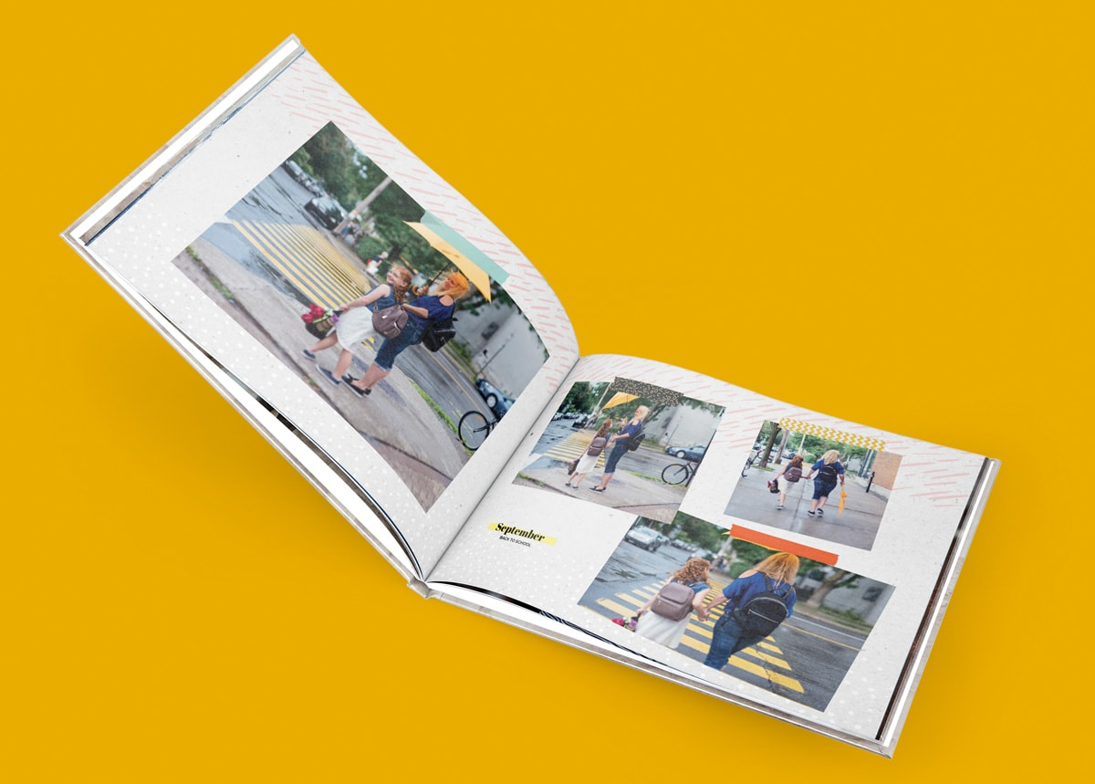 A family photo book open on a mustard yellow background with photos of a mother and daughter inside.