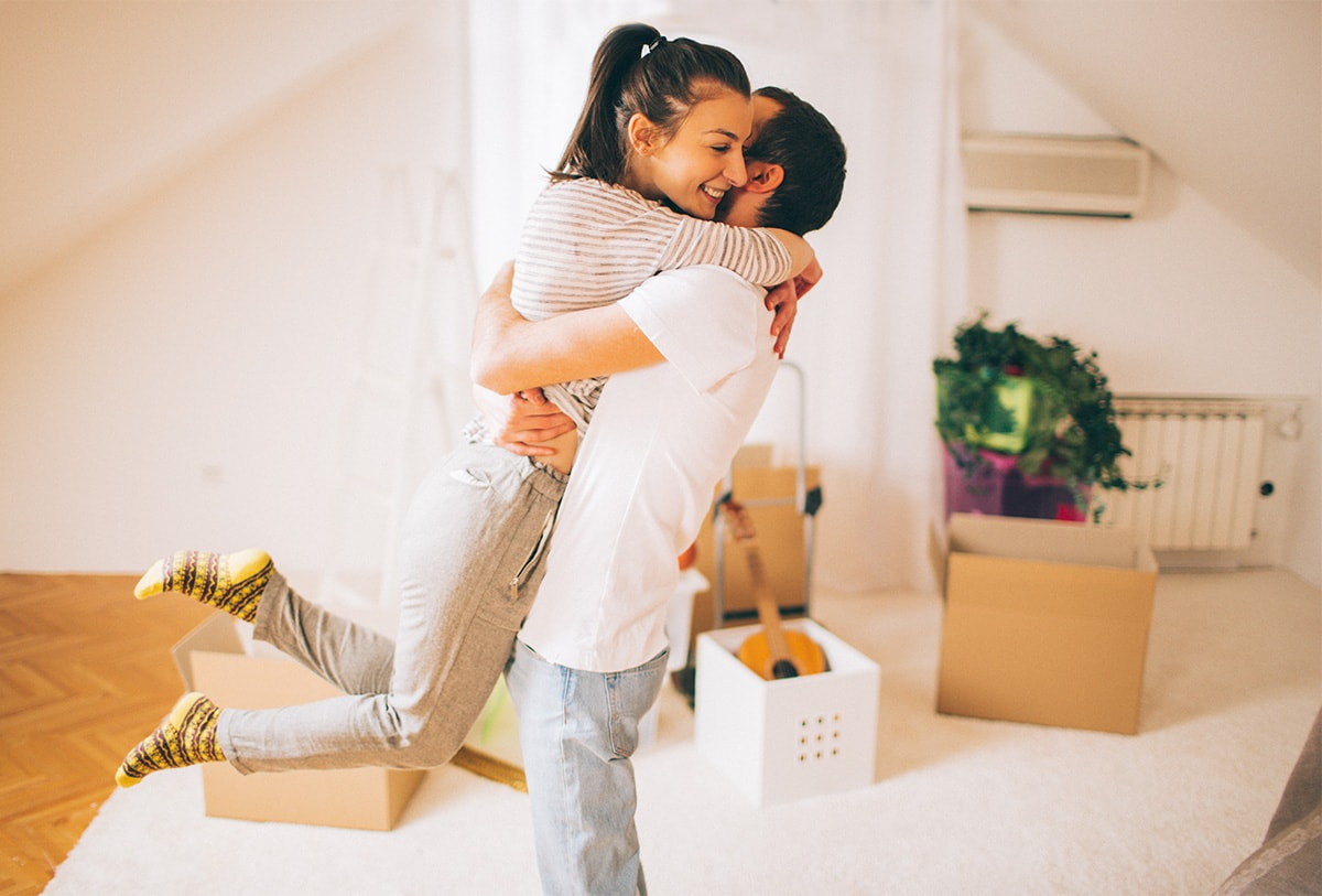 A photo of a young woman and man hugging in a new home, with moving boxes in the background.