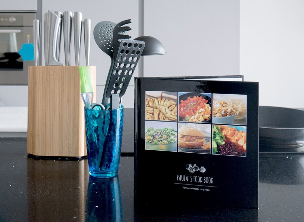 A recipe book stood up on a black kitchen counter top with cooking utensils and a knife block in the background.