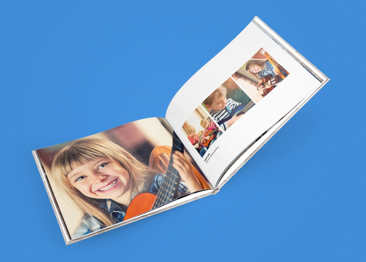 A photo book open against a bright blue background with a photo of a young girl inside playing the guitar.