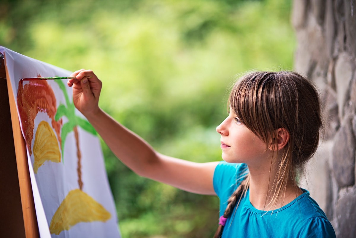 A photo of a young girl outside painting a beach scene on an easel.